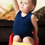 Toddler boy in blue sitting on red potty in front of a couch
