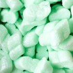 Green styrofoam packing peanuts in a shipping box