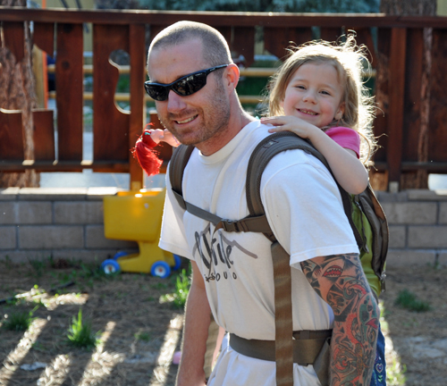 Brian wearing Zoe in the Onya Baby carrier in the back carry position