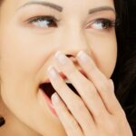 Yawning brunette woman with hand over her mouth