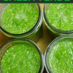 Four mason jars full of salsa verde that is being fermented on the counter