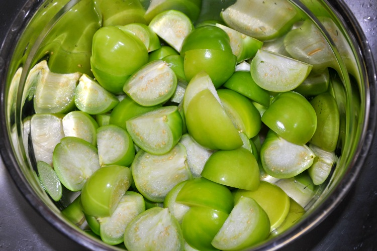Quartered tomatillos in a stainless steel mixing bowl