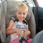 Kaylee buckled into her car seat while on a road trip