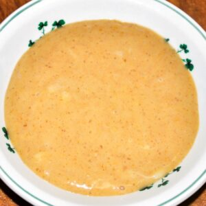 Overhead view of homemade pumpkin pudding in a white bowl with green embellishments