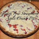Gluten free strawberry apple crumble pie on a wood cutting board