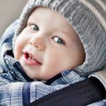 Smiling baby boy in winter clothes in car seat