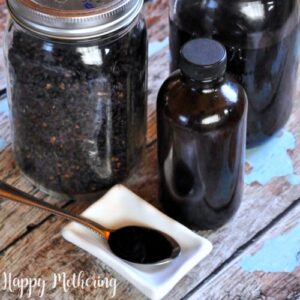 Mason jar of elderberries and a jar of homemadeelderberry syrup with some poured on a spoon