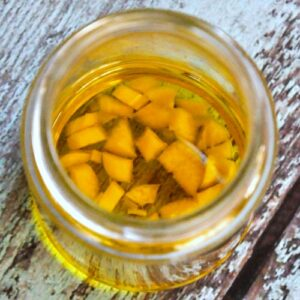 Glass jar filled with garlic oil for earaches