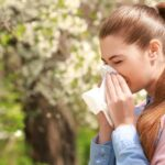 A woman standing in a field of flowering trees and sneezing from her allergies