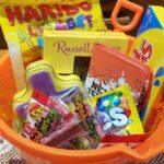 Orange sand bucket filled with Easter candy on a table