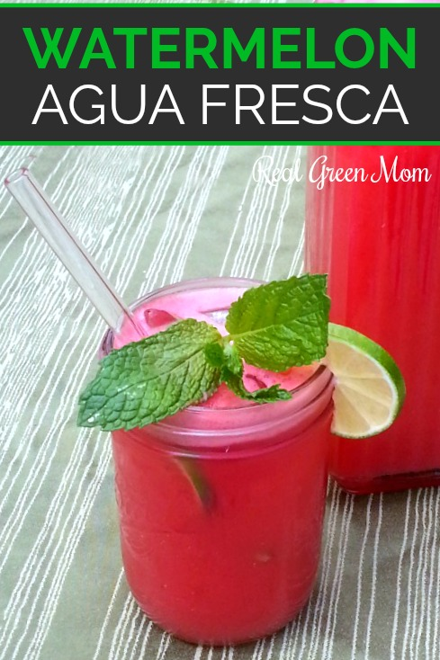 Watermelon agua fresca in pint sized mason jar with glass straw, garnished with mint and lime in front of full pitcher