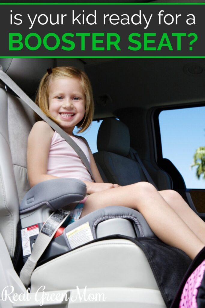 Little girl strapped into her booster seat in the back seat of a car