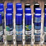 Sunlight shining on 18 blue roller bottles that have been labeled with essential oil blend name, decorated with washi tape and organized in a clear plastic lipstick organizer