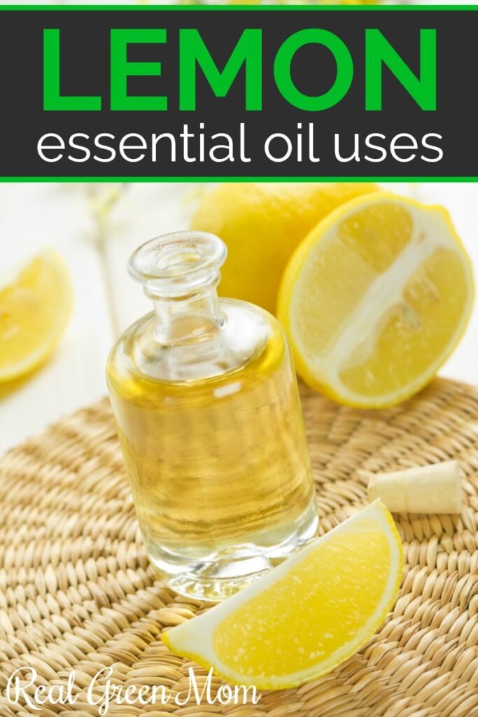Clear glass bottle of lemon essential oil with lemon wedges on a bamboo mat