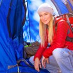 Young blond woman wearing beanie and red backpack squatting in front of her blue tent