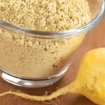 Close up of maca root powder in a clear glass bowl with maca root on the table next to it
