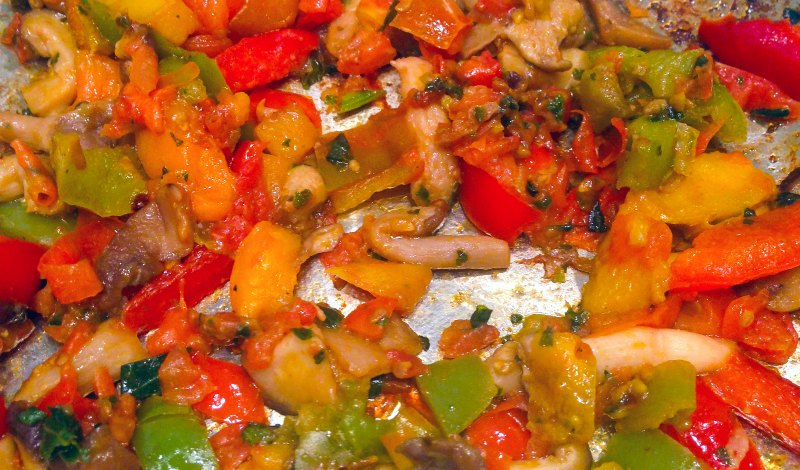 Peppers and onions being sauteed in a stainless steel pan
