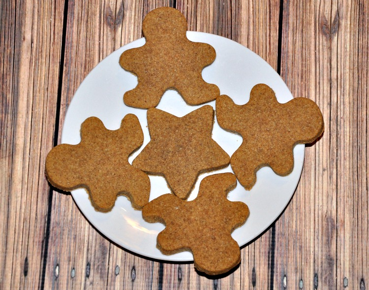 Four gingerbread man cookies on a white plate with a star cookie in the center