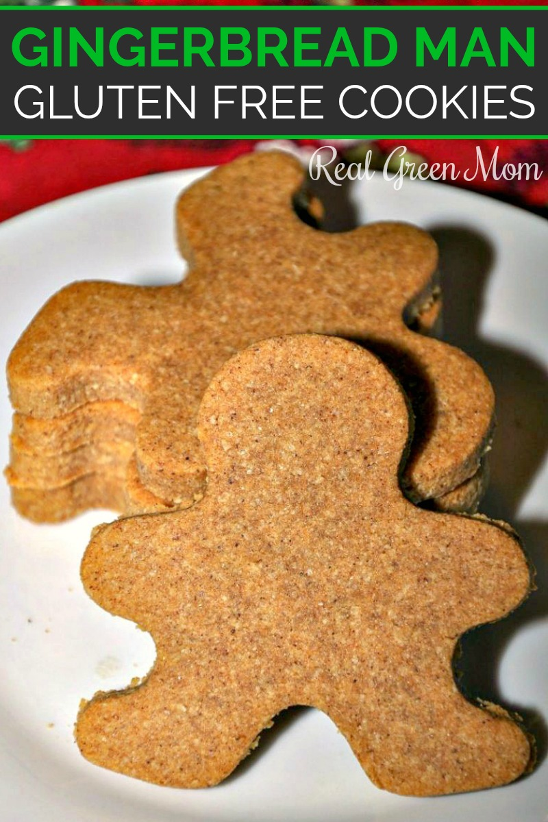 A stack of gingerbread man cookies on a white plate with one leaning up against the rest with a red background