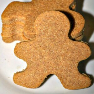 Close up of gingerbread man cookie leaned against a stack of three more on a white plate