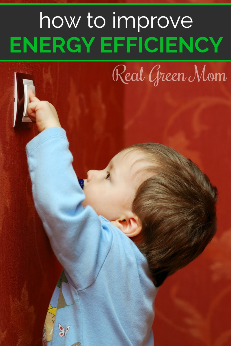 Little boy in blue pajamas turning on the light switch on a red wall