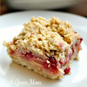 Close of of pomegranate apple pie bar with crumble topping on white dessert plate