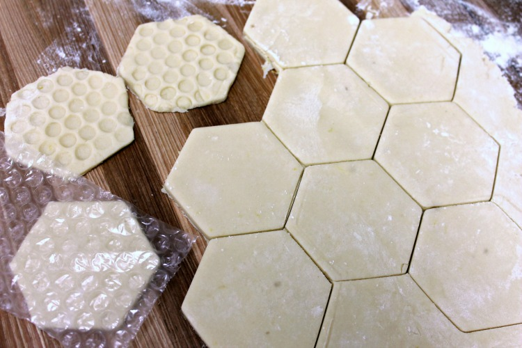 Hexagon shaped cookies being pressed with bubble wrap to make them look like honeycomb