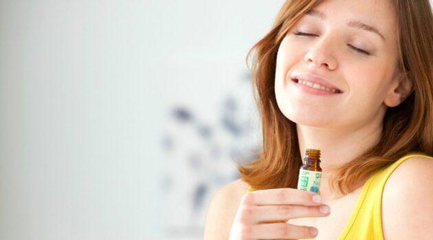 Brunette woman smelling bottle of essential oils