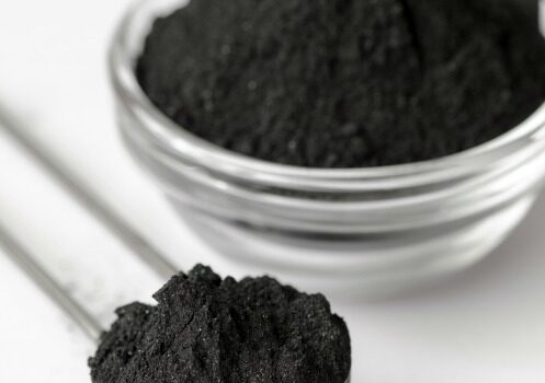 Activated charcoal in a glass bowl and measuring spoon