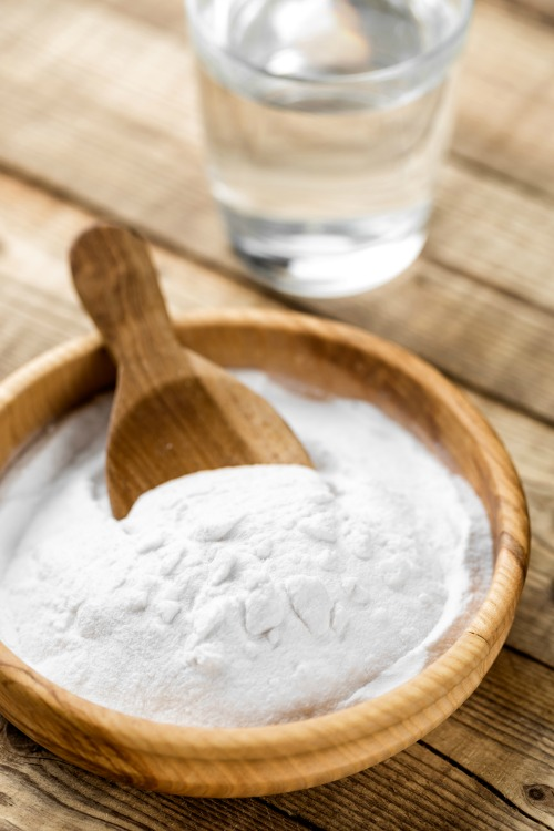 Baking soda in a wood bowl with a scoop