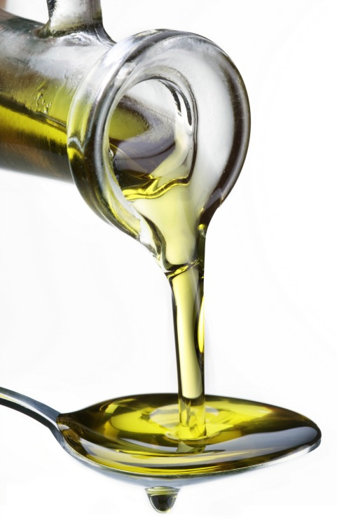 Olive oil being poured into a spoon