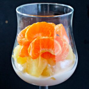Yogurt, pineapple and mandarin slices in a serving glass
