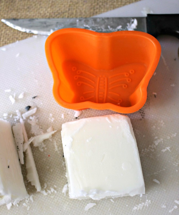 Orange silicone butterfly mold and melt and pour soap brick on a cutting board