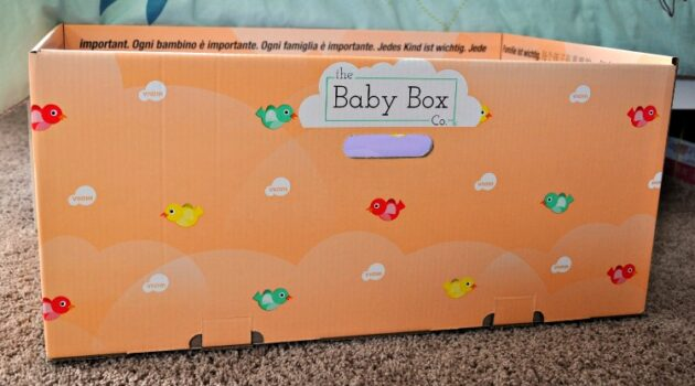 Side view of orange baby box on floor next to bed
