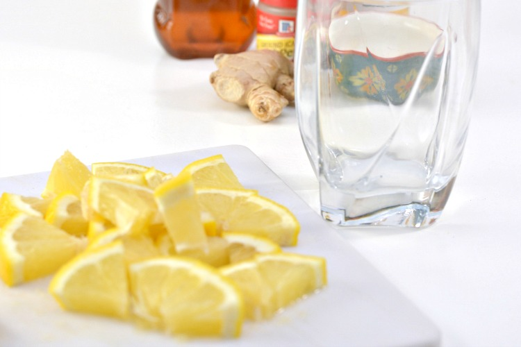 Glass next to lemon slices on a cutting board