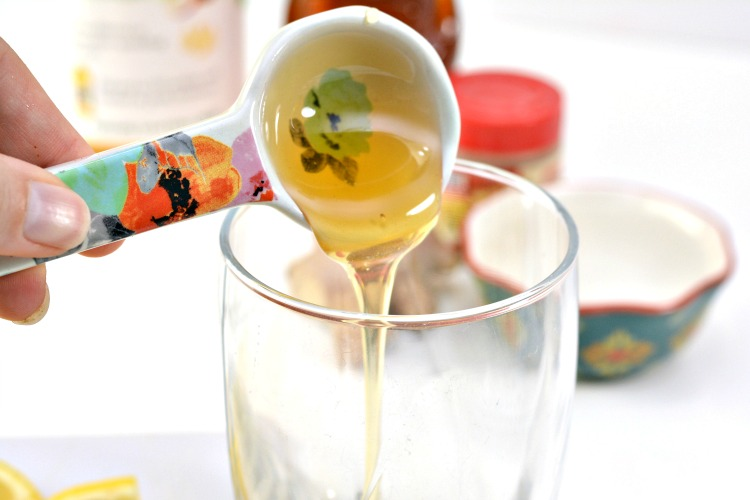 Raw honey in a tablespoon being added to a glass