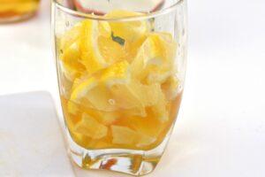 Lemon wedges added to glass with honey, apple cider vinegar and ginger