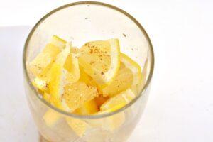 Cayenne pepper sprinkled over lemon wedges in glass