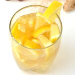 Glass of homemade lemon ginger tonic with a wedge on the rim