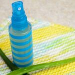 Spray bottle of after sun spray with aloe on a dishcloth