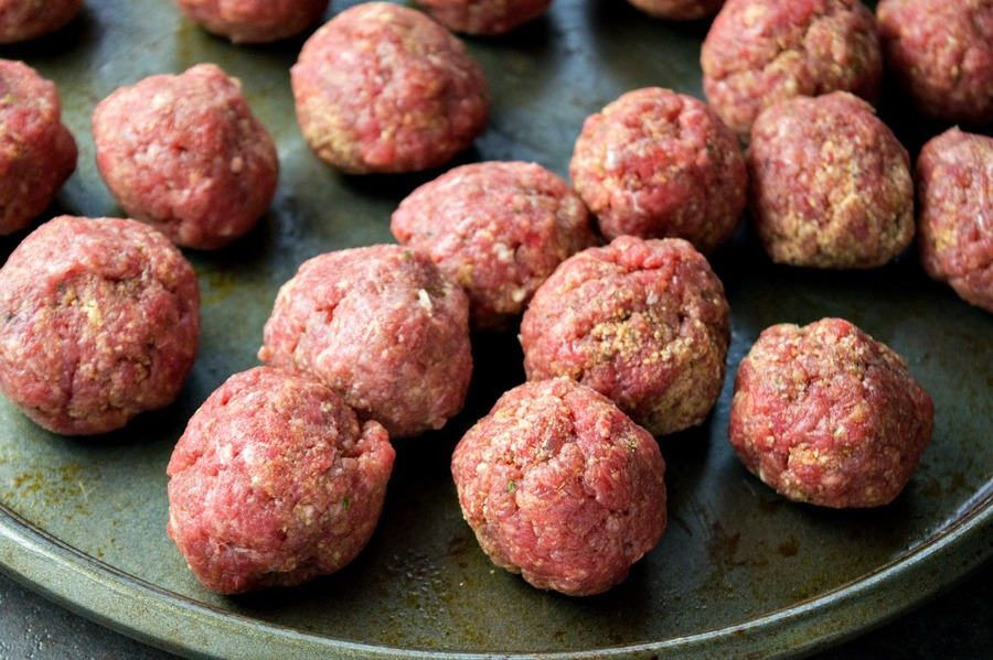 Small raw meatballs on a pan