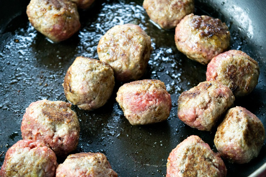 Meatballs cooking on a pan