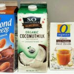 Chocolate almond milk, organic coconut milk and organic beef broth cartons on a fridge shelf