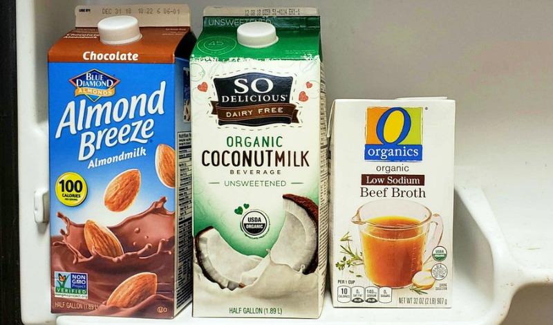 Chocolate almond milk, organic coconut milk and organic beef broth cartons on a fridge shelf