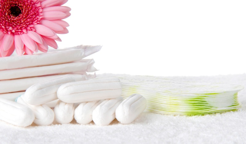 Organic pads and tampons on a white towel with pink flower