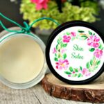 Open tub of homemade all purpose skin salve on a table