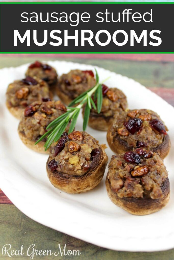 Serving platter of sausage stuffed mushroom with a rosemary sprig garnish
