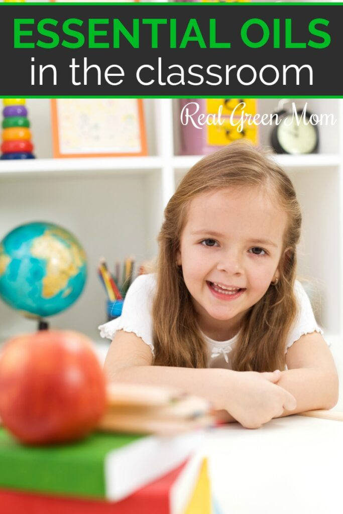Little girl sitting at her desk on the classroom with books, an apple, globe and more