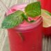 Close up of watermelon agua fresca served in pint sized mason jar with sprig of mint and slice of lime